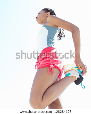 "Attractive ""african american"" woman stretching her legs while standing against a deep blue sky, exercising on a sunny day. - stock photo"
