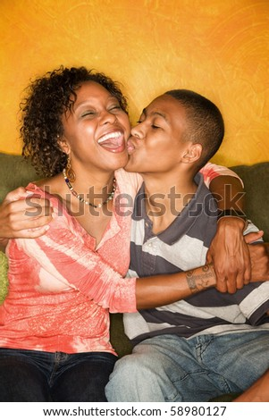 Attractive African-American woman with teen family member - stock photo