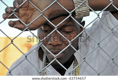 Attractive African American young man revealing his sadness and depression while leaning against a chain link fence. - stock photo