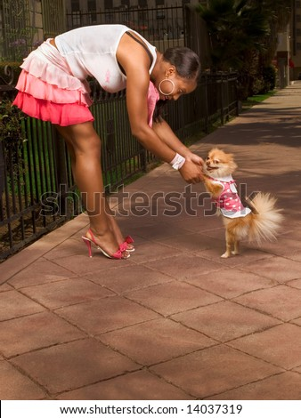 Attractive African-American young woman dancing with smiling small Pomeranian Spitz dog, that walks on rear legs, pink, skirt - stock photo