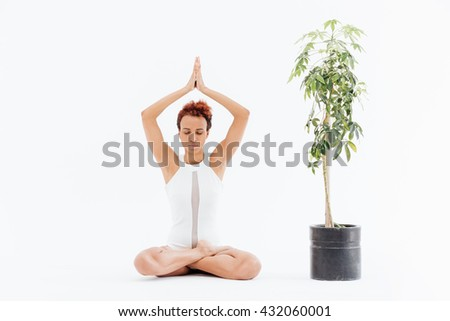 Attractive african american young woman sitting in lotus pose and practicing yoga near small tree in pot over white background - stock photo