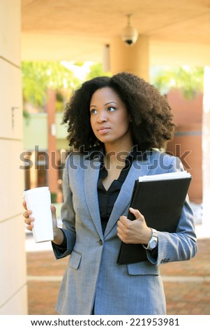 Attractive African AmericanBusiness Professional BusinessWoman with Black Hair Drinking Coffee Holding Folder  - stock photo