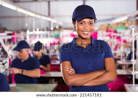 attractive african clothing factory worker with arms crossed - stock photo