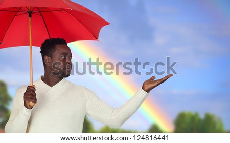 Attractive african man with a red umbrella and a beautiful rainbow