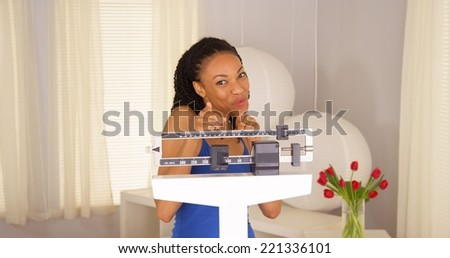 Attractive African woman dancing on scales - stock photo