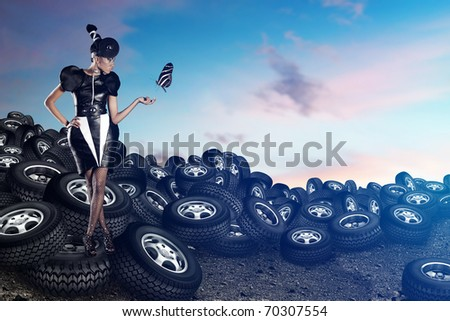 Attractive african woman on tires on the blue sky with betterfly - stock photo