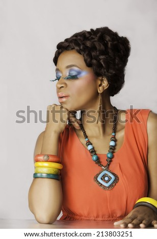 Attractive African woman posing with her chin on her hand, wearing colorful makeup, jewelry and bright coral colored dress - stock photo