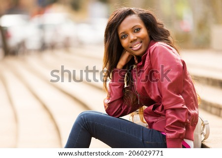 attractive african woman relaxing in urban city - stock photo