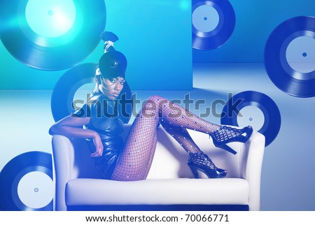 Attractive african woman siting in white chair on vinyl records and neon light - stock photo