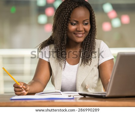 Attractive african woman sitting at the table in coworking centre and using laptop. - stock photo