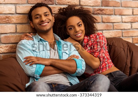 Attractive Afro-American couple looking in camera and smiling while sitting on beanbag chairs against brick wall - stock photo