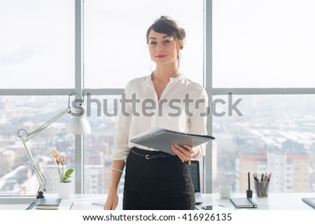 Attractive ambitious businesswoman standing in modern office, holding paper folder, looking at camera, smiling. - stock photo