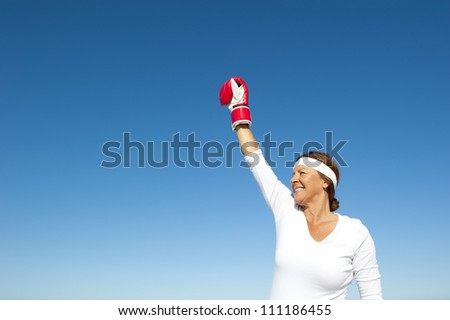 Attractive and active senior woman in victory pose with boxing glove, feeling confident and fit after exercising, isolated with blue sky as background and copy space. - stock photo