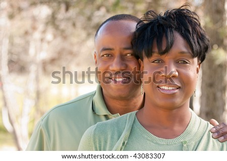 Attractive and Affectionate African American Couple posing in the park. - stock photo