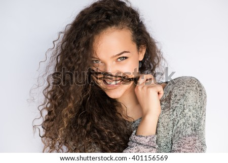 Attractive and beautiful portrait of young woman smiling and doing a mustache with a hair strand - stock photo