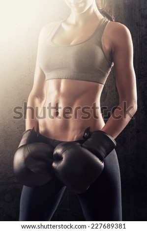 Attractive and fit girl with boxing gloves in training - stock photo