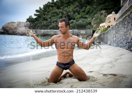 Attractive and fit young bodybuilder in bathing suit kneeling on the beach - stock photo