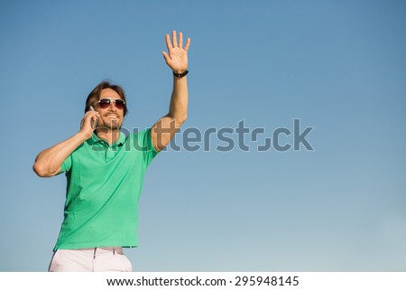 """Attractive and handsome businessman using mobile phone. Man in sunglasses saying """"Hello"""" to his partners in the distance. - stock photo"""