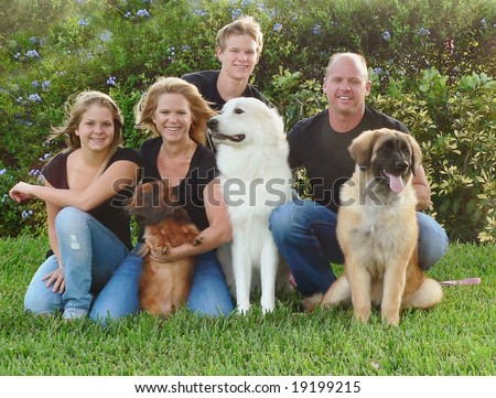 Attractive and happy family with their dogs sitting on a lawn.  The family consists of Mom, Dad, brother and sister.  They are dressed in matching black shirts with blue jeans.  It is a breezy day. - stock photo