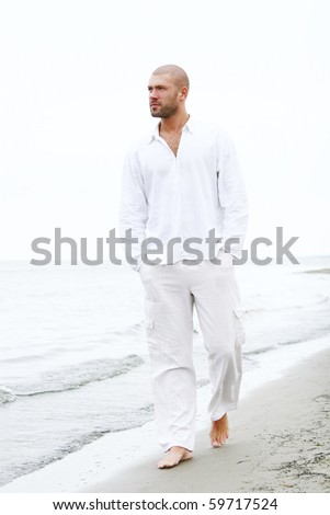 attractive and happy man on the beach - stock photo