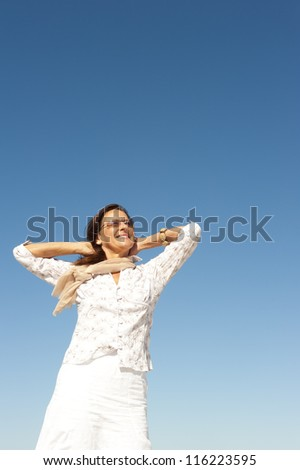 Attractive and happy middle aged woman relaxed and casual enjoying active retirement, isolated with blue sky as background and copy space.