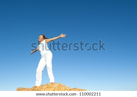 Attractive and joyful mature woman with open arms standing on top of a rock, isolated with blue sky as background and copy space.