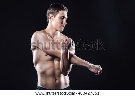 Attractive and muscular athlete. Studio shot of young shirtless sportsman on black background. Man stretching - stock photo