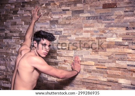 Attractive and muscular shirtless young man leaning against stone wall - stock photo