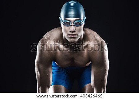Attractive and muscular swimmer ready to jump into water. Studio shot of young shirtless sportsman on black background. Man with glasses - stock photo