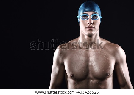 Attractive and muscular swimmer. Studio shot of young shirtless sportsman on black background. Man with glasses - stock photo