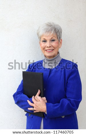 Attractive and Retired Mature Professional Business Woman Smiling and Holding a Folder - stock photo