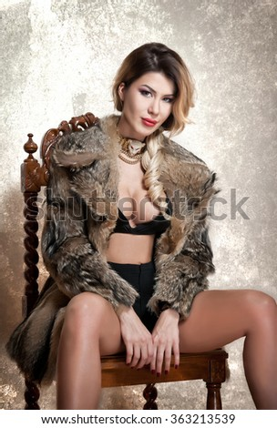 Attractive and sexy blonde woman with black lingerie and fur coat posing provocatively sitting on chair, gray background. Sensual female with fair hair and beautiful legs looking into the camera  - stock photo