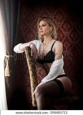 Attractive and sexy blonde woman with black lingerie and white sweater posing sitting on chair near a window. Sensual female with fair hair and long black stockings looking on the window in daylight - stock photo