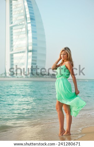 Attractive and sexy european professional young model girl posing on sandy beach in dress in tropical country - stock photo
