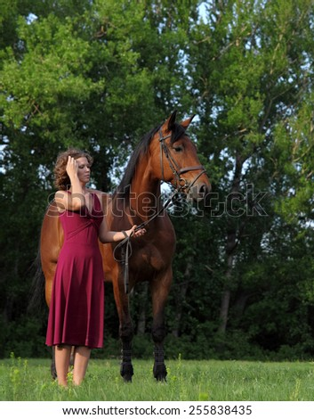Attractive and shapely redhead woman with horse - stock photo
