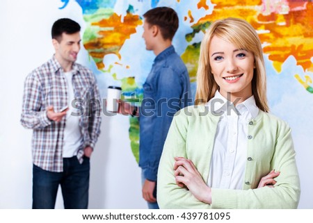 Attractive and smart student. Confident young woman keeping arms crossed and looking at camera with smile while his colleagues talking in the background. - stock photo