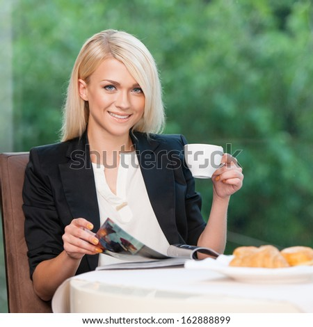 Attractive and stylish lady having breakfast. Reading magazine looking at camera  - stock photo