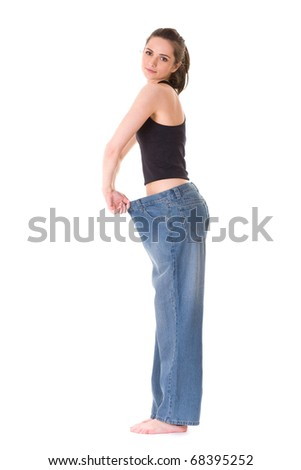 attractive and young female shows her old huge pair of jeans, weight loss concept, studio shoot isolated on white - stock photo
