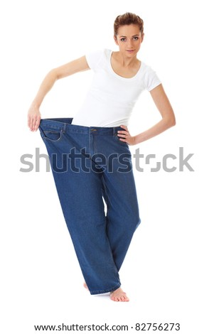 attractive and young female shows her old huge pair of jeans, weight loss concept, studio shoot - stock photo