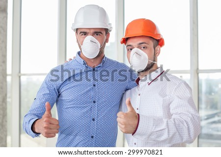 Attractive architect and cheerful foreman are working in respirators and helmets. They are giving thumbs up with joy. The men are embracing and looking at the camera happily - stock photo