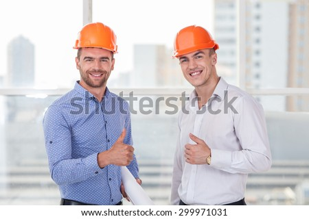 Attractive architect and foreman are giving thumbs up. The customer approved a plan of building. They are smiling happily - stock photo