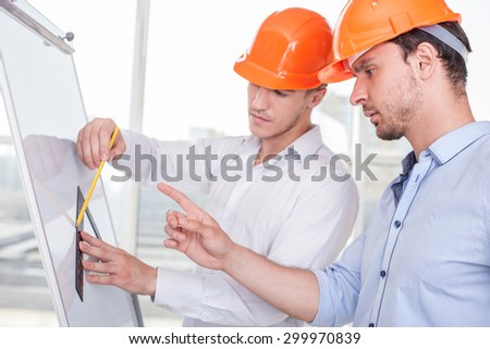 Attractive architects are working on a project. One builder is drawing sketches on blueprint with inspiration. Another man is pointing his finger at it and giving advices concerning a plan seriously - stock photo
