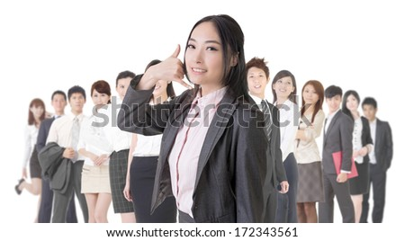Attractive Asian business woman give you a phone call sign and stand in front of her team.
