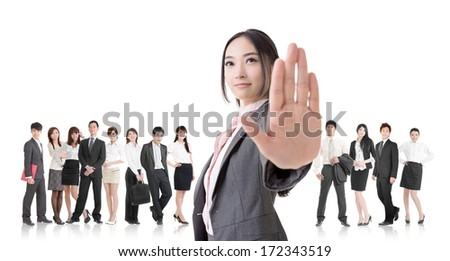Attractive Asian business woman give you a stop sign and stand in front of her team.