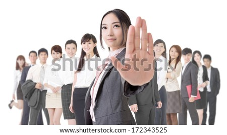 Attractive Asian business woman give you a stop sign and stand in front of her team. - stock photo