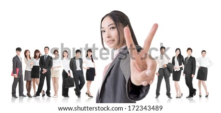 Attractive Asian business woman give you a victory sign and stand in front of her team. - stock photo