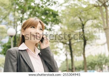 Attractive Asian business woman talk on phone under green tree in modern city, closeup portrait shot at Xinyi business district, Taipei, Taiwan. - stock photo