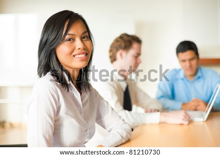 Attractive Asian businesswoman looking at the camera sitting at conference room table in meeting with diverse group of business people including a Latino and Caucasian male. Horizontal