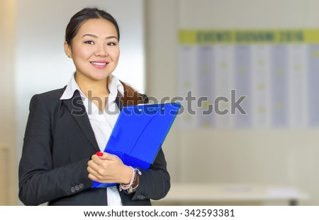 Attractive Asian businesswoman smiling and holding a folder in her office - stock photo