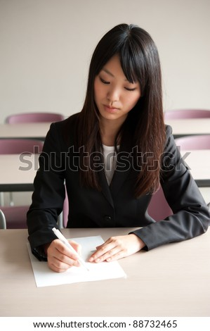 attractive asian businesswoman writing in the office